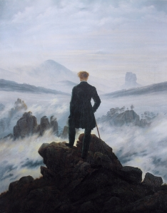 A man stands atop a mountain looking down at the clouds