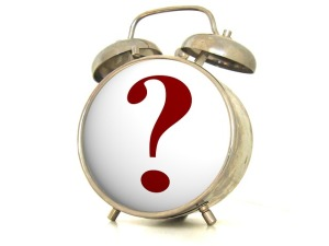 Old fashioned alarm clock with a question mark on its face.