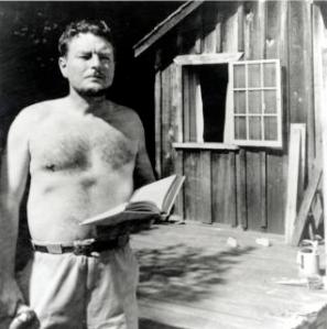 A shirtless Malcolm Lowry stands beside his shack in 1940s Dollarton, British Columbia. He is holding an open book.